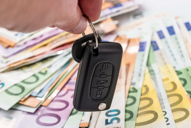 Mãos com a chave do carro em dinheiro do euro
