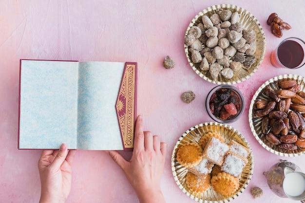 Mãos com alcorão na mesa com doces
