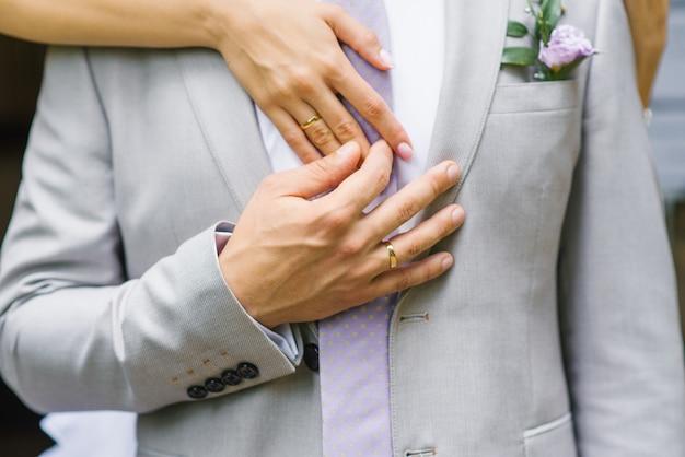 Mãos com alianças de casamento close up dos noivos. um homem segura a mão da noiva
