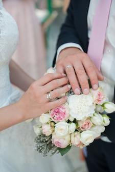 Mãos com anéis com um buquê de casamento