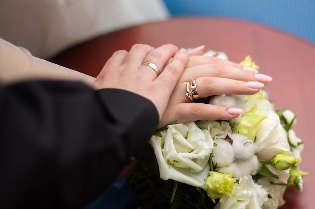 Mãos com anéis de casamento em um buquê de rosas brancas