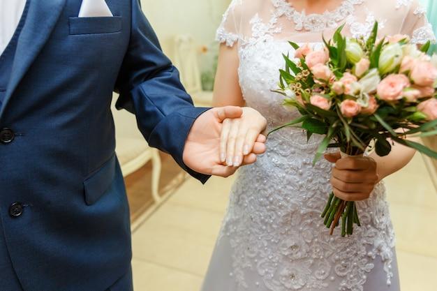 Mãos com anéis. o noivo acompanha a noiva até a cerimônia de casamento.
