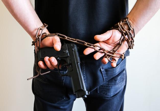 Mãos com arma em velhas correntes enferrujadas. ladrão preso por crime ilegal. o assaltante infringiu a lei.