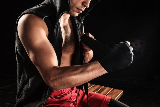Mãos com bandagem de homem musculoso treinando kickboxing no preto