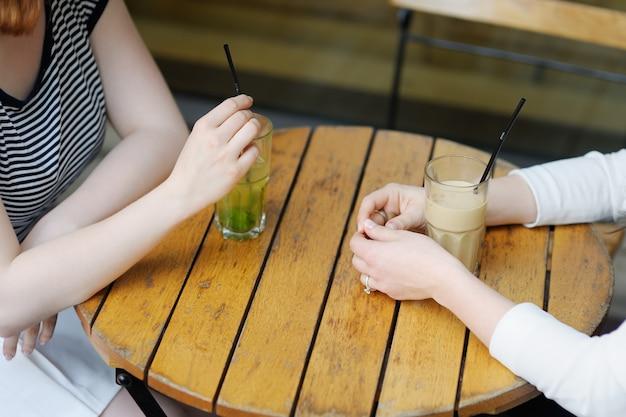 Mãos com bebidas de duas meninas