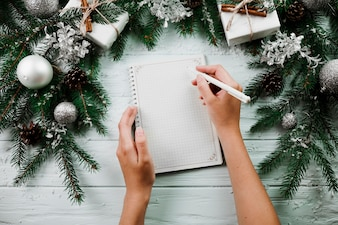 Mãos, com, caderno, perto, ramos natal
