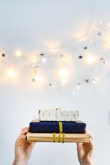 Mãos com caixas de presentes perto de luzes de fada e estrelas de ornamento