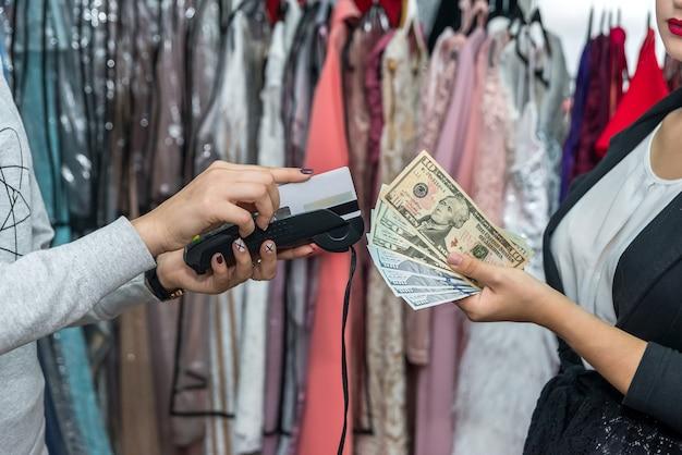 Mãos com cartão de crédito e dólares, pagamento