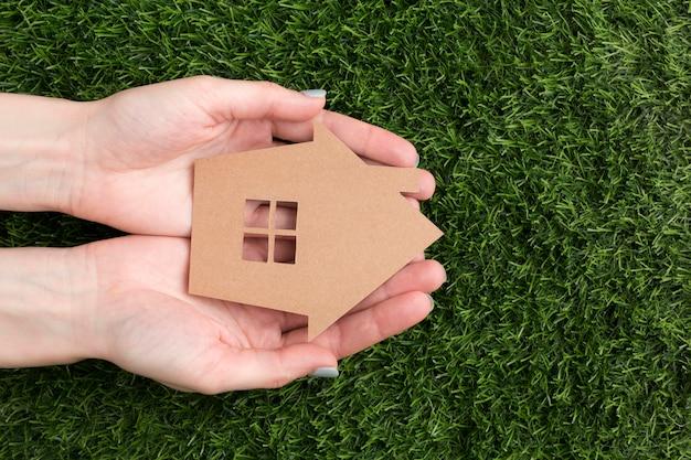 Mãos com casa em miniatura