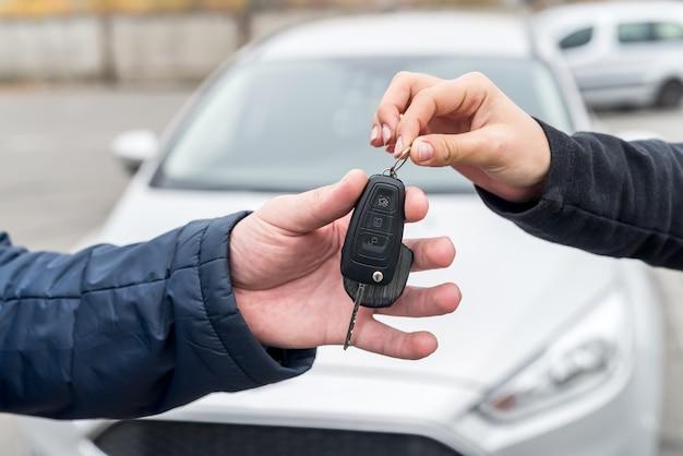 Mãos com chaves contra carro novo close-up