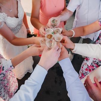 Mãos com copos de champanhe amigos no casamento