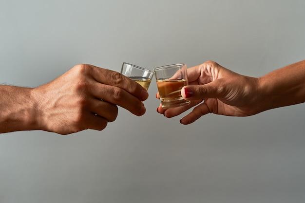 Mãos com copos de shot brindando. conceito de alcoolismo e dependência.