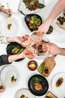 Mãos com copos de vinho rosé para uma família, jantar amigável no estilo asiático. bolinhos de massa, rolinhos primavera, macarrão wok, bifes, saladas