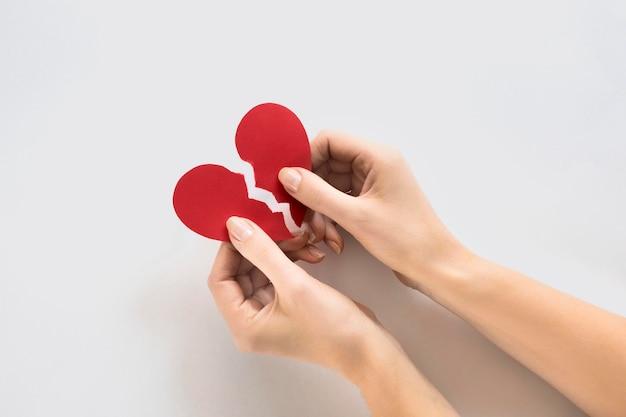 Mãos com coração de papel quebrado