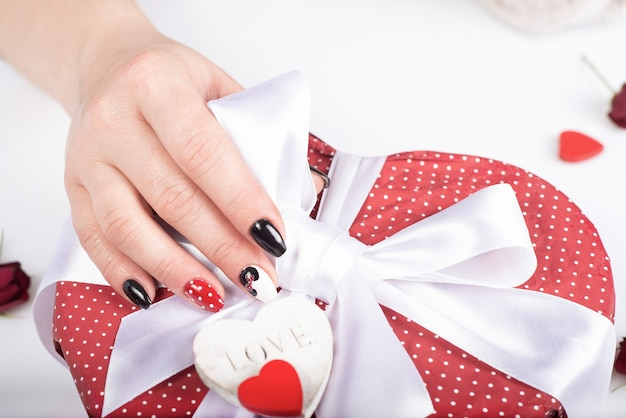 Mãos com elegante gel manicure caixa de presente aberta com laço.