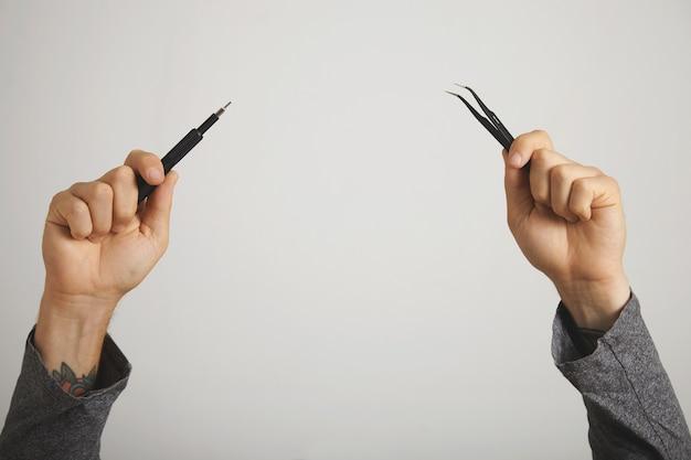 Mãos com ferramentas de conserto de computador - chave de fenda e pinças - levantadas no ar