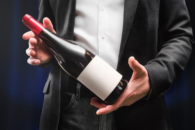 Mãos com garrafa de vinho. oferta. garçom. sommelier