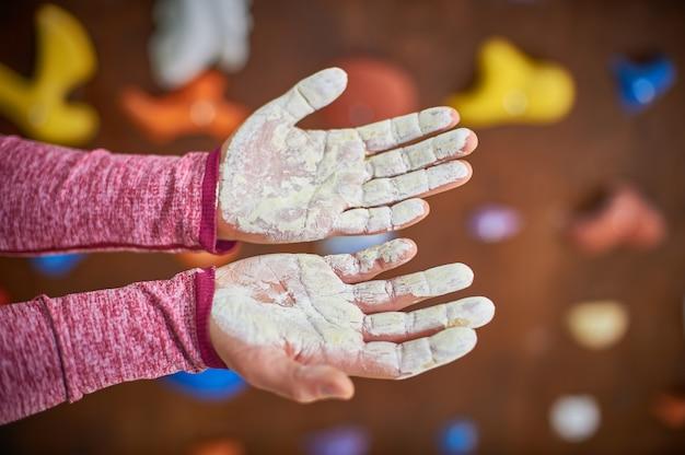 Mãos com giz líquido bouldering sobre parede de escalada turva