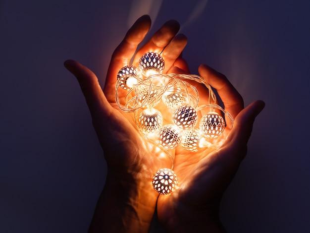 Mãos com lâmpadas. lâmpadas de metal com padrão delicado brilham no escuro. decoração do feriado com reflexos de luz mágicos.