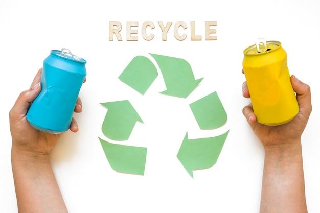 Mãos com latas e reciclar letras com logotipo