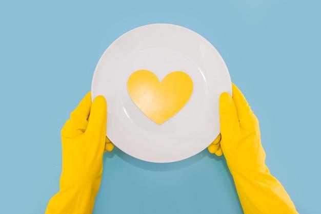 Mãos com luvas amarelas seguram um prato branco com um coração amarelo isolado em um fundo azul. vista de cima.