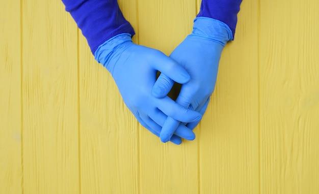 Mãos com luvas azuis fecham na desinfecção de mão.