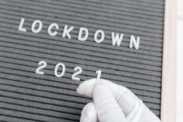 Mãos com luvas brancas seguram o número 1, substituindo o número zero pelo número um no bloqueio de texto da mensagem 2020.