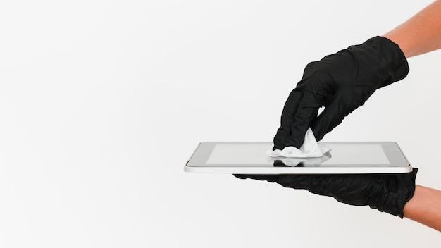 Mãos com luvas cirúrgicas desinfetando tablet com espaço de cópia