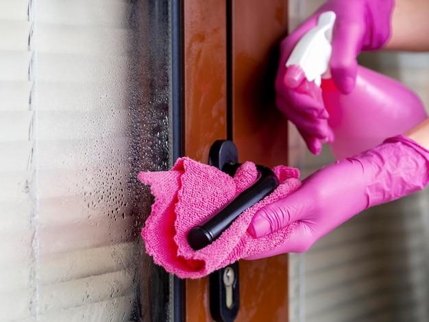 Mãos com luvas cirúrgicas, maçaneta da porta de limpeza com ablução