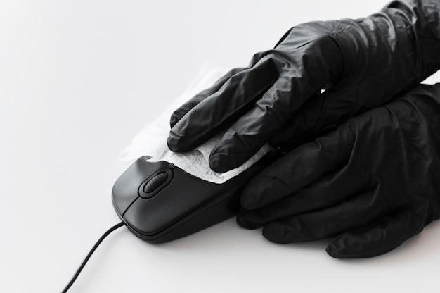 Mãos com luvas cirúrgicas para desinfecção de mouse