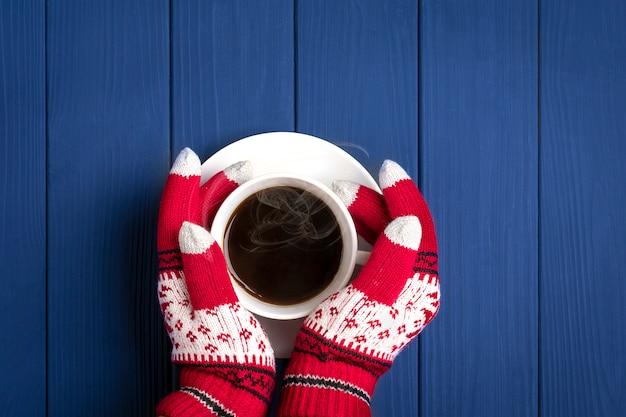 Mãos com luvas com padrão de ano novo segurar uma xícara branca com café quente na superfície de madeira azul