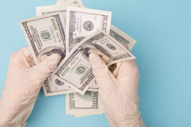 Mãos com luvas de borracha segurando uma pilha de dinheiro
