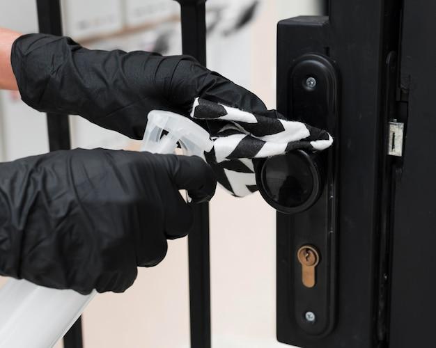 Mãos com luvas de desinfecção da alça do portão