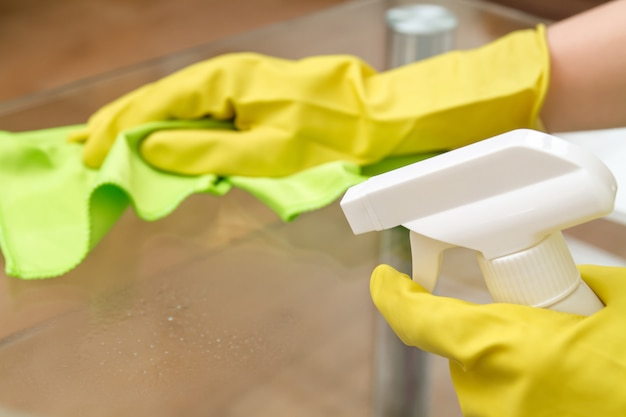 Mãos com luvas de proteção com pano e spray limpando a mesa de centro de vidro