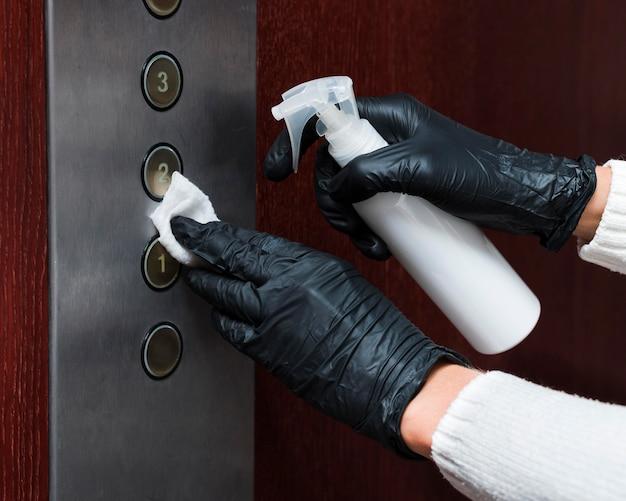 Mãos com luvas desinfetando botões de elevador