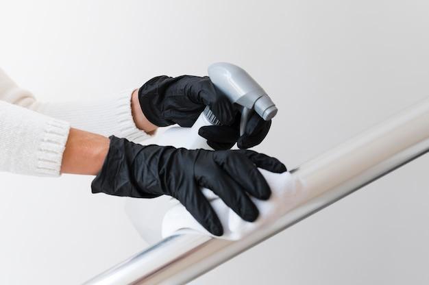 Mãos com luvas desinfetando corrimão