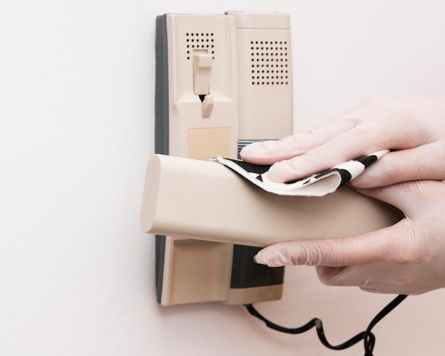 Mãos com luvas desinfetando interfone
