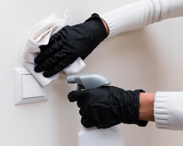 Mãos com luvas desinfetando interruptor de luz