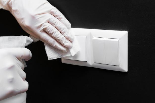 Mãos com luvas desinfetando interruptores de luz
