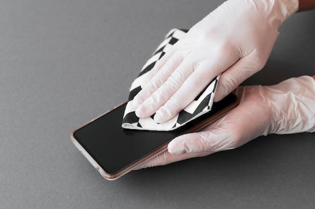 Mãos com luvas desinfetando smartphone