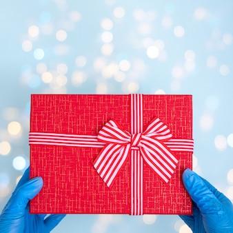 Mãos com luvas médicas azuis segurando uma caixa de presente vermelha com fita isolada em azul
