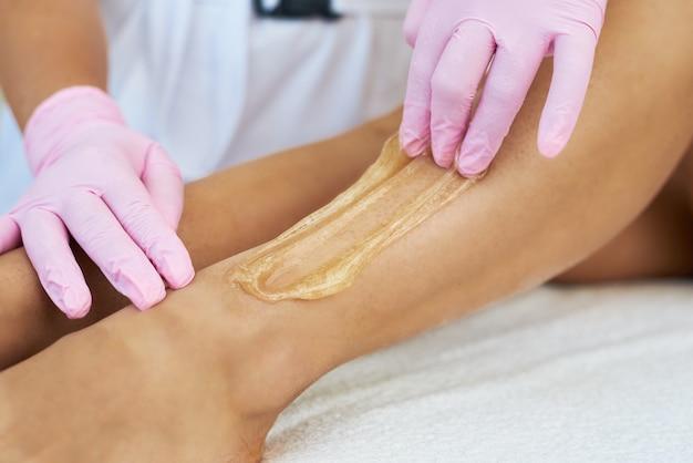 Mãos com luvas rosa aplicando creme depilatório em uma perna