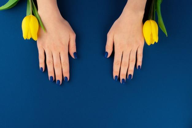 Mãos com manicure segurando tulipas amarelas