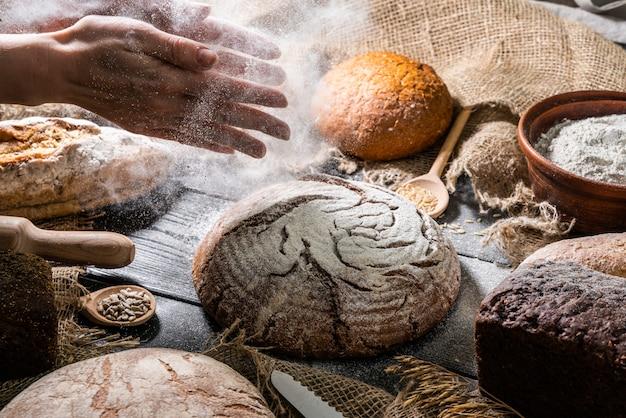 Mãos com pão na mesa de madeira escura