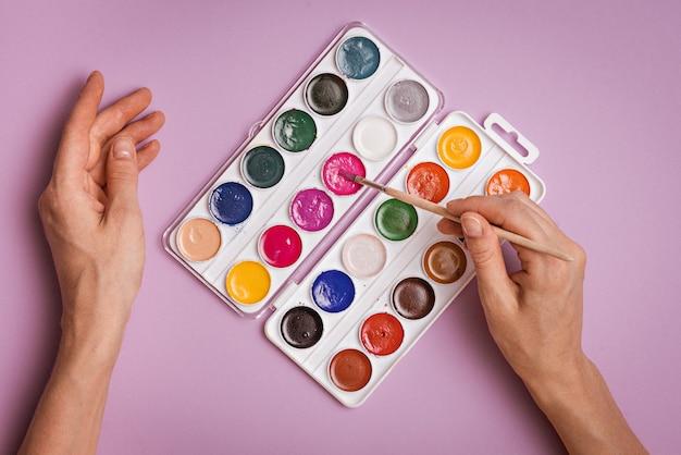 Mãos com pincel e paleta de cores em aquarela sobre fundo rosa, vista superior, trabalho criativo, conceito de criatividade de inspiração de pintura de arte