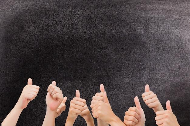 Mãos com polegares para cima gesto contra um quadro-negro