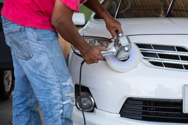 Mãos com polidor orbital, polir carro branco. detalhamento do carro e conceito de lavagem.