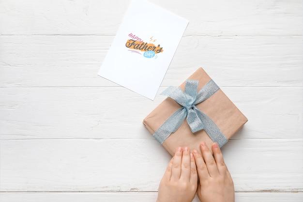 Mãos com presente para o dia dos pais e cartão comemorativo em fundo branco de madeira