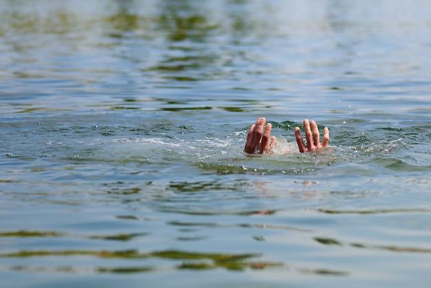 Mãos com salpicos de água se afogando homem. copie o espaço.