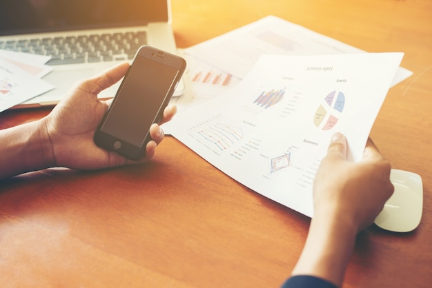 Mãos com smartphone e documentos